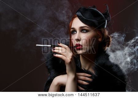 Beautiful young woman with smoky eyes and full red lips holding cigarette holder. Vintage head piece. Retro styling. Studio beauty shot over smoky background. Copy space.