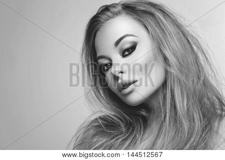 Closeup portrait of beautiful young woman with messy long blond hair and bright makeup. Beauty shot over grey background.