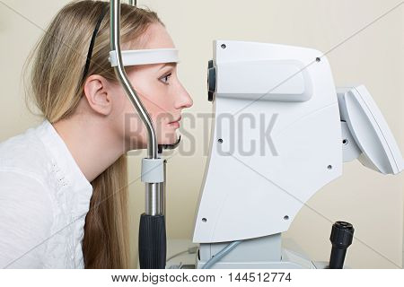Optometry concept -  young woman having her eyes examined by an eye handsome elderly doctor. Topography of the cornea