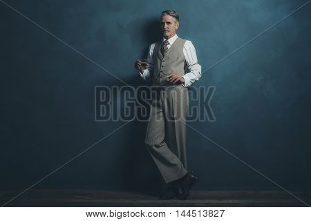 Businessman Retro 1920S Style Holding Glass Of Whiskey And Cigar. Leaning Against Wall.
