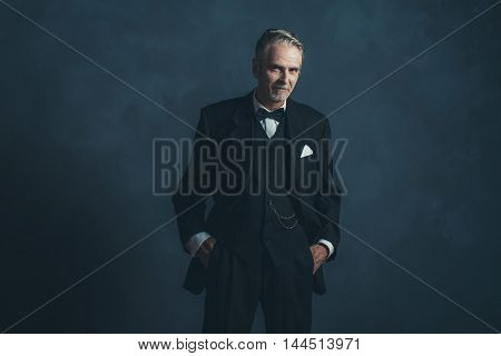 Confident Middle Aged Retro 1920S Businessman In Black Suit With Bow Tie.