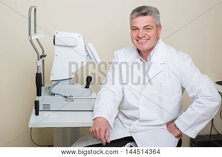 Optometry concept -  portrait of handsome elderly eye doctor