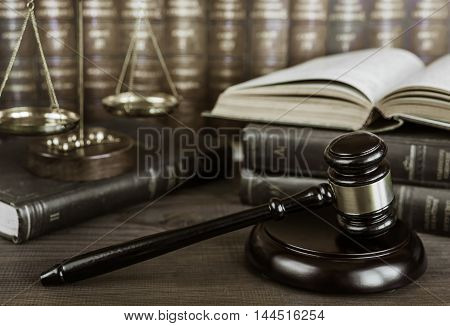 Wood gavel soundblock scales and open old book against the background of a row of antique books bound in leather