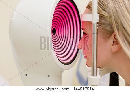 Optometry concept -  young woman having her eyes examined by an eye handsome elderly doctor. Topography of the cornea.