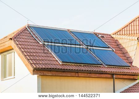 Vacuum collectors- solar water heating system on red roof of the house. poster