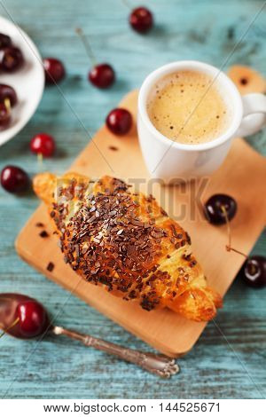 Tasty breakfast with fresh croissant, coffee and cherries on a wooden table. Selective focus on croissant.