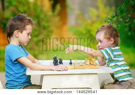 chess dispute. two boys playing chess outdoors