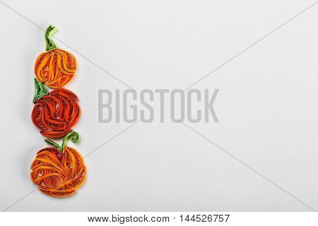Pumpkin in quilling techniques for Halloween on a light background