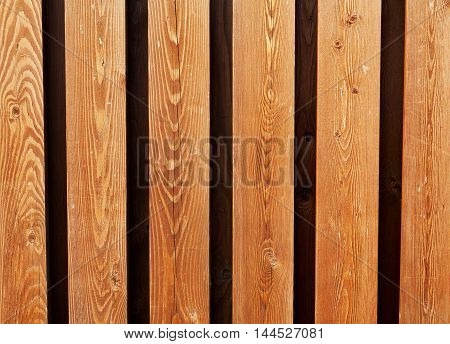 Wooden fence from yellow deals for natural background. Building concept. Panel lumber material.