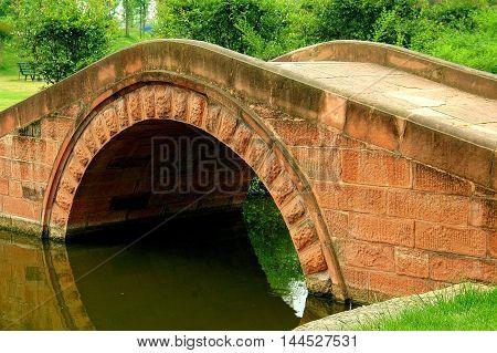 Sanxindui / Sichuan China - April 29 2006: Coral-colored single arched sandstone bridge spans a canal at the Sanxiungdui Ancient Shu Civilisation Museum