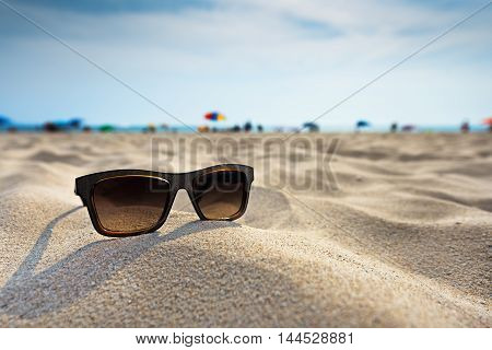 Sun glasses lie on a beach near the sea.