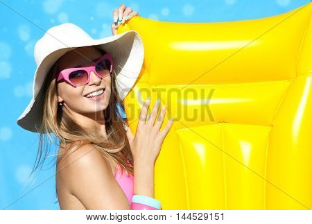Summer beach style portrait a beautiful smiling happy young blonde woman wearing hat, bikini and sunglasses with inflatable swimming pool toys
