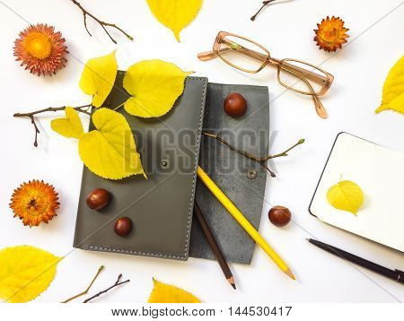 Closeup of leather pen case notebook and glasses on white background. Decorated with autumn yellow leaves flowers and branches. Top view flat lay