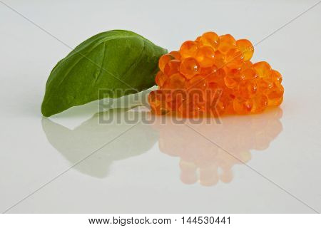 Trout roe and basil leaf on a white plate close up with copy space, imaging with focus stacking