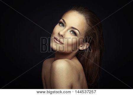 Woman beauty portrait on dark background toned image