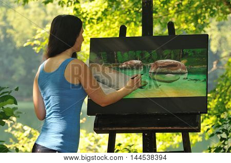 female artist painting nature scene with acrylic paint on canvas