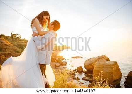 Attractive bride and groom getting married by the beach at sunset