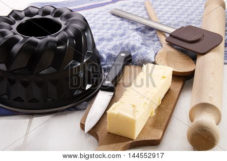 125 grams butter stick ideal for baking with a knife on a wooden board