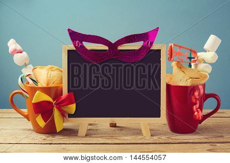 Purim holiday background with chalkboard and traditional gifts