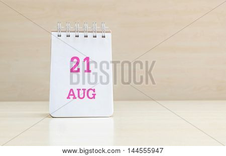 Closeup surface note book with pink 21 aug word in page on blurred brown wood desk and wood wall textured background with copy space under window light