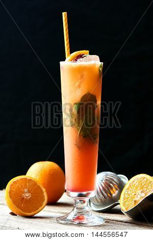 The glass of alcoholic cocktail sex on the beach homemade cranberry, mint, orange and peach juice on wooden table on black background