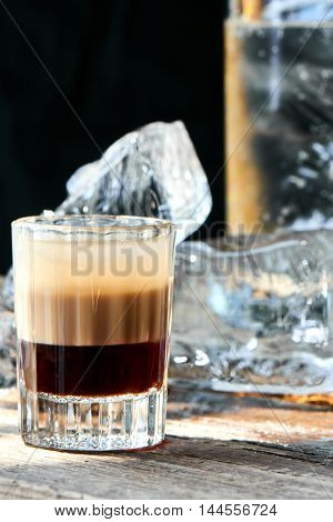 Alcoholic cocktail B-52 in the glass on wooden table