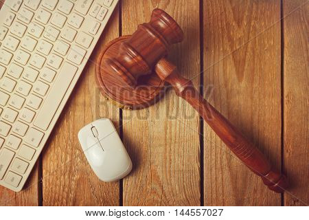 Judge gavel and computer keyboard on wooden vintage background