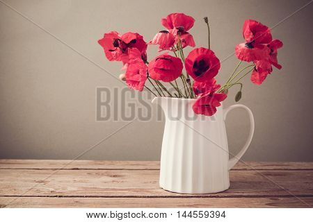 Red poppy flower bouquet in white jug on wooden table