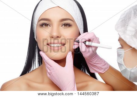 Young Woman before Plastic Surgery Operation Cosmetology. Doctor does line on a female face before plastic surgery. Beautician touching woman face. Beauty Face. Isolate on white background