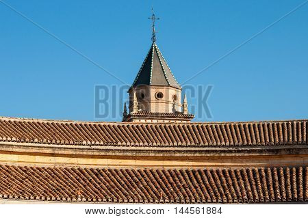 View of the tiled roof of the Courtyard of the Palacio de Carlos Vl in Spain in the city of Granada on the blue sky.