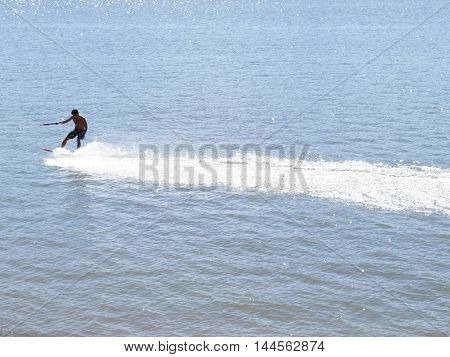 man skiing radically in the lake, water foam