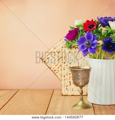 Passover background with matzo wine and flowers on wooden table