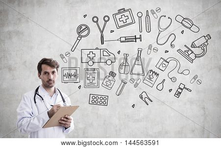 Man doctor with stethoscope and clipboard standing near concrete wall with medical sketches on it. Concept of modern medicine and healthcare