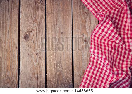 Wooden old table with checked tablecloth. View from above