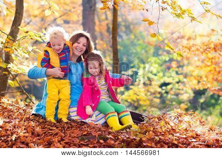 Mother and kids play in autumn park. Parent and children walk in the forest on a sunny fall day. Boy and girl playing outdoors with yellow maple leaf. Toddler picking golden leaves. Mom hugging kid.