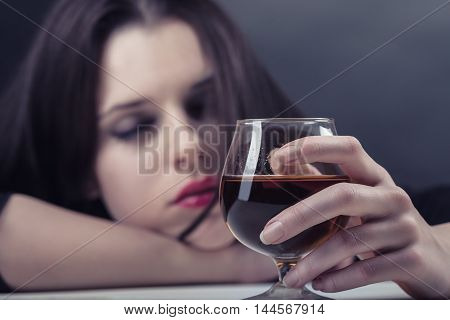 Young beautiful woman in depression drinking alcohol on dark background. Focus on the glass