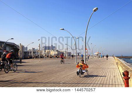 TEL AVIV, ISRAEL - APRIL 1, 2016: Local people on bicycle on new promenade in Tel Aviv port, Israel.
