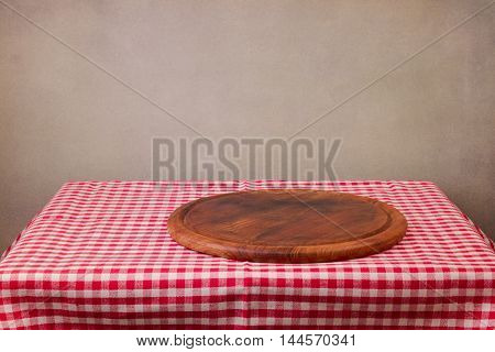 Wooden board on table with red checked tablecloth