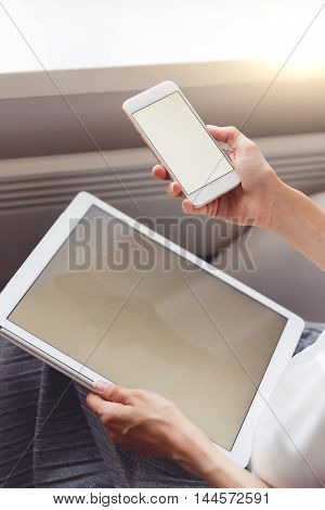 Woman using tablet and smartphone, empty computer screen for your design copy space. Image with lens flare effect and split toned