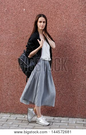 Portrait of flirty beautiful brunette young woman with backpack, stylish modern look