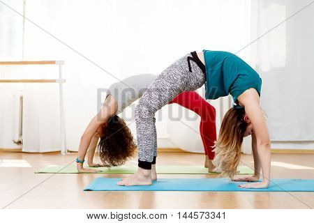 Portrait of two beautiful young girls doing back bend pose in yoga class