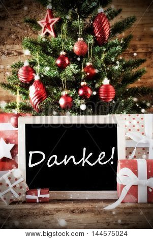 Christmas Card For Seasons Greetings. Christmas Tree With Balls. Gifts Or Presents In The Front Of Wooden Background. Chalkboard With German Text Danke Means Thank You