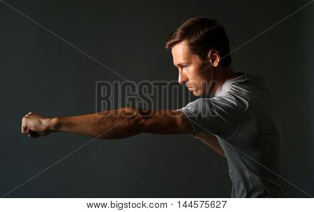 Side view of young handsome man making punches. Low key photography.