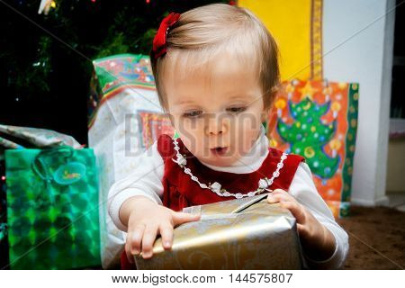 A baby examines her Christmas present on her first Christmas. She has a look of awe on her face.
