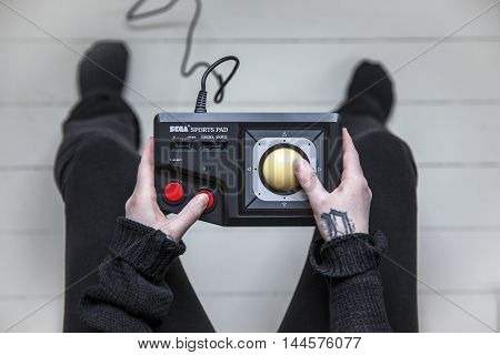 Gothenburg, Sweden - February 20, 2016: A woman's hands holding a Sports Pad controller, a controller for the video game console Sega Master System developed by Sega Games Co., Ltd. in the 1980s.