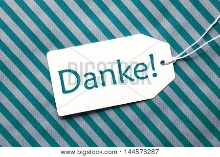One Label On A Turquoise Striped Wrapping Paper. Textured Background. Tag With Ribbon. German Text Danke Means Thank You