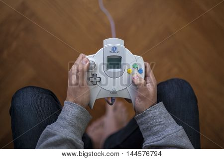 Gothenburg, Sweden - January 24, 2015: A shot from above of a young mans hands holding a game controller for the Sega Dreamcast, a game console developed by Sega Enterprises, Inc. in the late 1990s.
