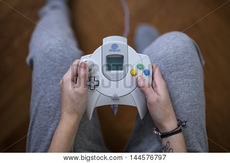 Gothenburg, Sweden - January 24, 2015: Shot from above of a young womans hands holding a game controller for the Sega Dreamcast, a game console developed by Sega Enterprises, Inc. in the late 1990s.