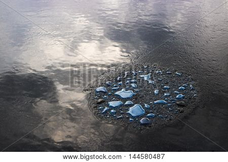 Abstract of blue oil stains on dark ground in light rain.