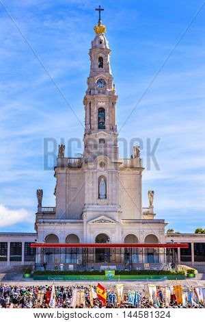 FATIMA, PORTUGAL - MAY 11, 2014 May 13th Celebration of Mary's Appearance Banners Pilgrims Basilica of Lady of Rosary Bell Tower Fatima Portugal. Church created on site where three Portuguese Shepherd children saw Virgin Mary of the Rosary. Basilica creat